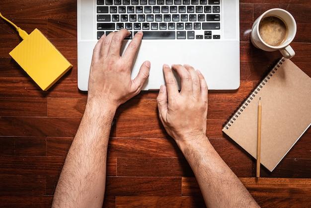 Ręka mężczyzny wpisująca klawiaturę na laptopie z boku znajduje się kubek do kawy, notes, ołówek i żółty zewnętrzny dysk twardy.