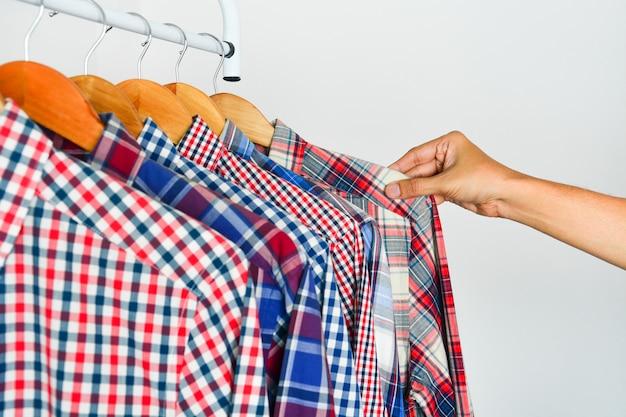 Ręka mężczyzny wybiera czerwoną, niebiesko-białą kraciastą koszulę z długim rękawem na drewnianym wieszaku