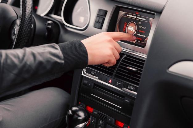 Ręka mężczyzny wybiera styl jazdy na komputerze pokładowym samochodu.