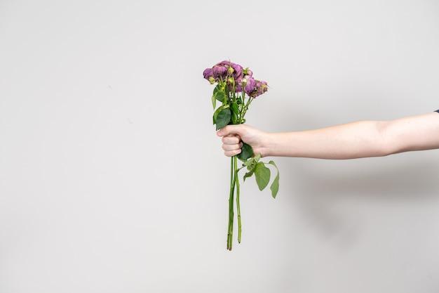 Ręka mężczyzny wyciąga bukiet zwiędłych kwiatów. koncepcja separacji. układ z miejscem na tekst