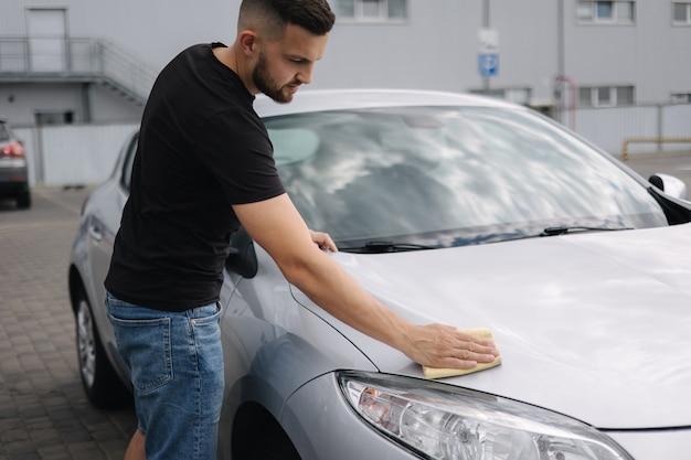 Ręka mężczyzny wyciera reflektor swojego samochodu za pomocą myjni samoobsługowej z dywanami na zewnątrz