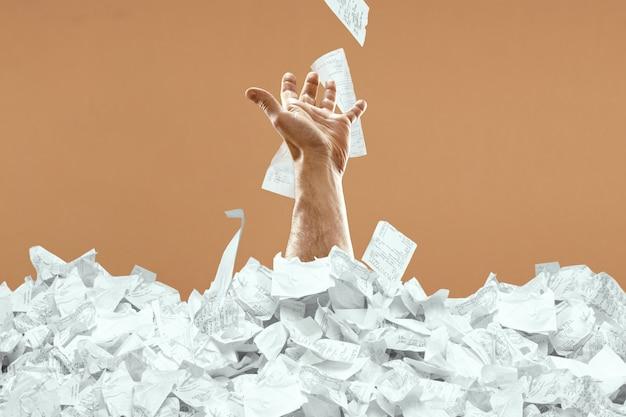 Ręka mężczyzny wystaje z góry czeków i rachunków. człowiek tonie w długach, kredycie, hipotece, pożyczce, hipotece.