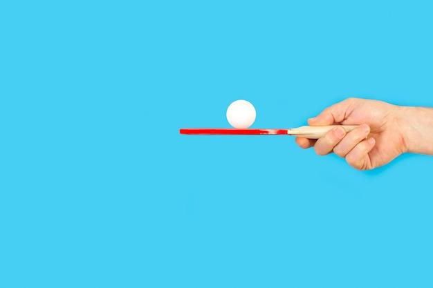 Ręka mężczyzny z czerwoną wiosłem do ping ponga z białą piłką na niebiesko