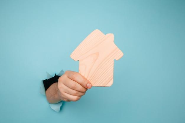 Ręka mężczyzny z drewnianym modelu domu przez otwór w niebieskim papierze. koncepcja sprzedaży i wynajmu domu