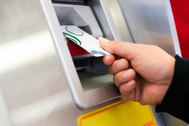 Ręka mężczyzny z kartą kredytową, za pomocą bankomatu. obsługuje używać bankomat z jego kartą kredytową.