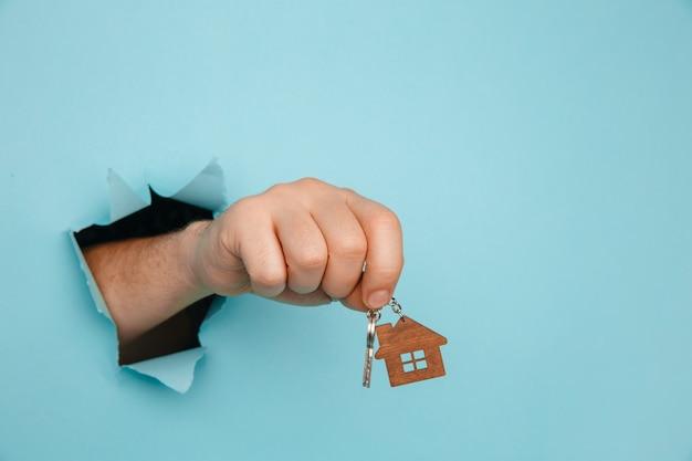Ręka mężczyzny z kluczami do domu przez otwór w niebieskim papierze