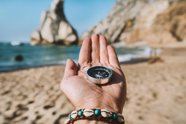 Ręka mężczyzny z kompasem symbolizującym koncepcję poszukiwania przygód