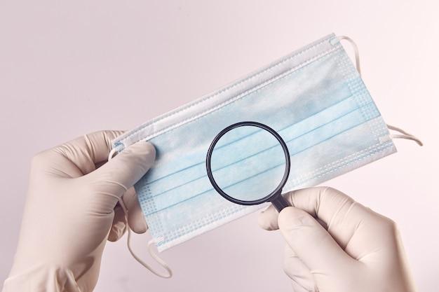 Ręka mężczyzny z lateksową rękawicą używa szkła powiększającego z maską chirurgiczną