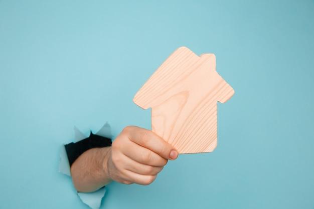 Ręka mężczyzny z modelem domu przez otwór w niebieskim papierze. koncepcja sprzedaży i wynajmu domu.