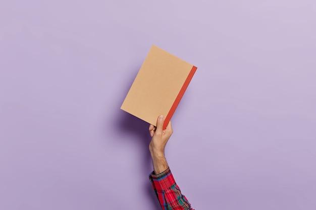 Ręka mężczyzny z pustym pamiętnikiem na białym tle nad fioletem