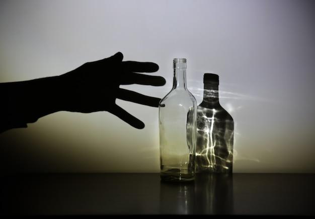 Ręka mężczyzny z sylwetką butelki alkoholu. uzależniony od alkoholu. niebezpieczny nawyk. koncepcja niezdrowego życia. problem społeczny.