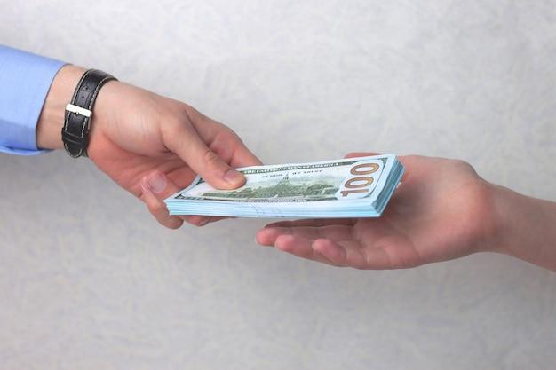 Ręka mężczyzny z zegarkiem daje kobiecie zwitek pieniędzy.