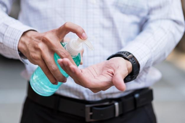 Ręka mężczyzny za pomocą dozownika żelowego środka do dezynfekcji rąk, przeciwko nowemu koronawirusowi lub chorobie wirusowej corona (covid-19) w miejscach publicznych.