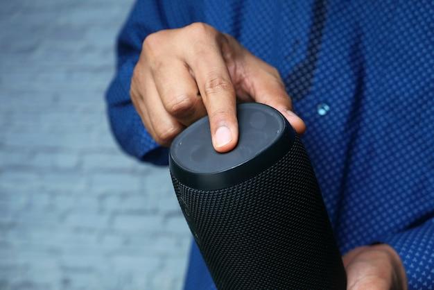 Ręka mężczyzny za pomocą inteligentnego głośnika z bliska