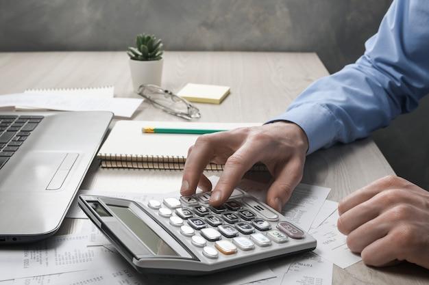 Ręka mężczyzny za pomocą kalkulatora i pisania notatek z obliczaniem kosztów i podatków w biurze domowym