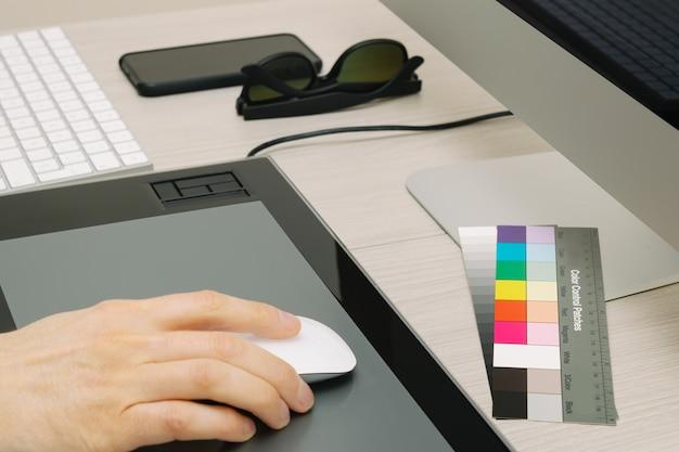 Ręka mężczyzny za pomocą myszy, z kolorowymi łatami, okularami i smartfonem na stole roboczym