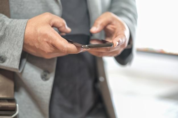 Ręka mężczyzny za pomocą telefonu komórkowego
