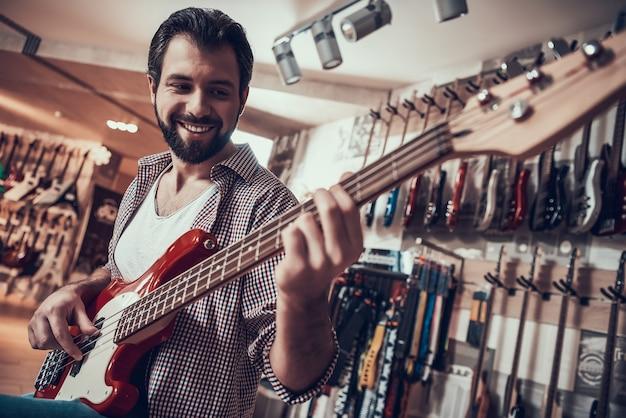 Ręka mężczyzny zaciska struny w progu gitary elektrycznej. strojenie gitary.
