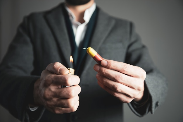 Ręka mężczyzny zapalając petardy na białym tle