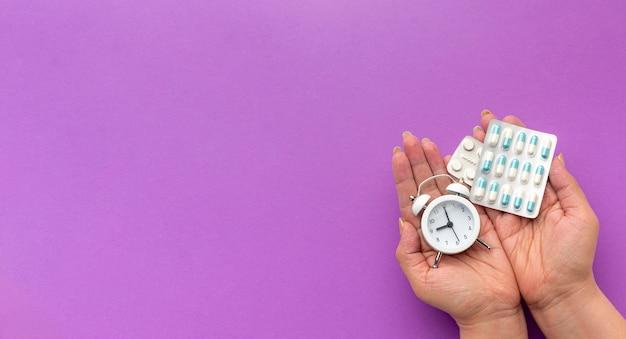 Ręka miejsce z zegarem i pigułki
