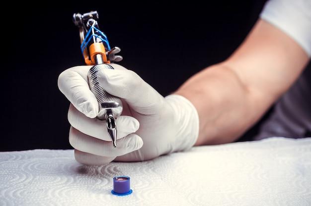 Ręka mistrza sztuki tatuażu i maszynki do tatuażu.