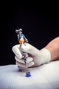 Ręka mistrza sztuki tatuażu pistoletem do tatuażu