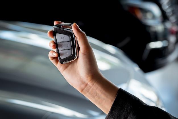 Ręka młoda biznesowa kobieta trzyma klucz nowy samochód wśrodku przedstawicielstwa firmy samochodowej - sprzedawczyni samochodów, fachowa usługa