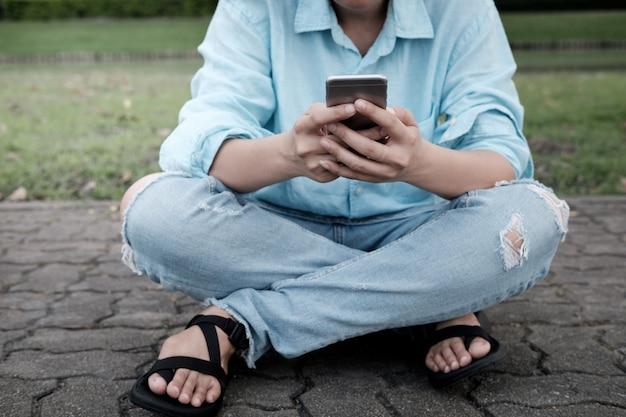 Ręka młoda modniś kobieta używa mądrze telefon na ceglanej drodze