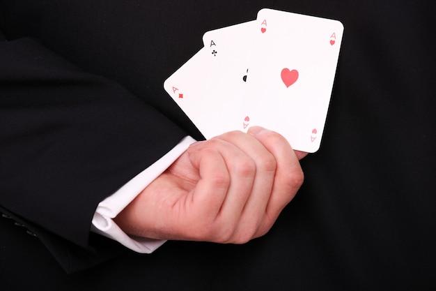 Ręka młodego biznesmena trzymająca trzy asy za plecami