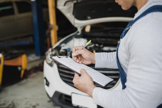 Ręka młodego człowieka mechanika mienia schowka lista kontrolna samochód przy usługowego centrum naprawą