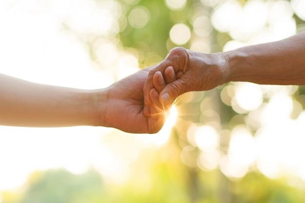 Ręka młodego człowieka mienia ręka starsza osoba