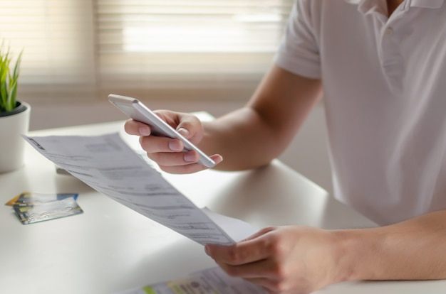 Ręka młodego człowieka za pomocą inteligentnego telefonu komórkowego do skanowania i płatności online z rodzinnymi rachunkami kosztów budżetu na biurku w domowym biurze, plan oszczędności pieniędzy, inwestycji, finansów biznesowych, koncepcja wydatków