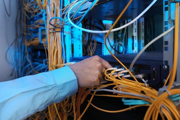 Ręka młodego inżyniera łącząca kable w serwerowni