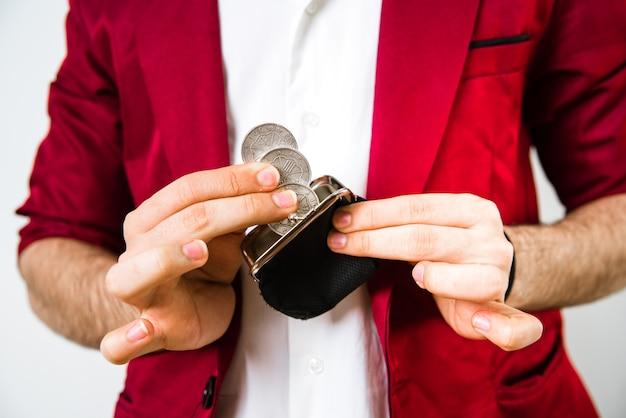 Ręka młodego mężczyzny wyjmuje monety z małej torebki, aby coś kupić.