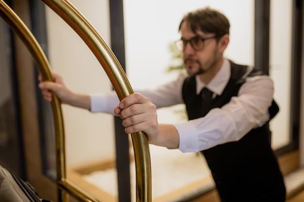 Ręka młodego tragarza trzymającego się za uchwyty podczas pchania wózka i odbierania bagażu gości hotelowych