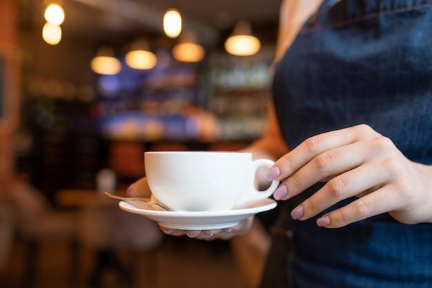 Ręka młodej kelnerki z filiżanką herbaty lub kawy, niosąca ją jednemu z klientów podczas pracy we współczesnej restauracji lub kawiarni