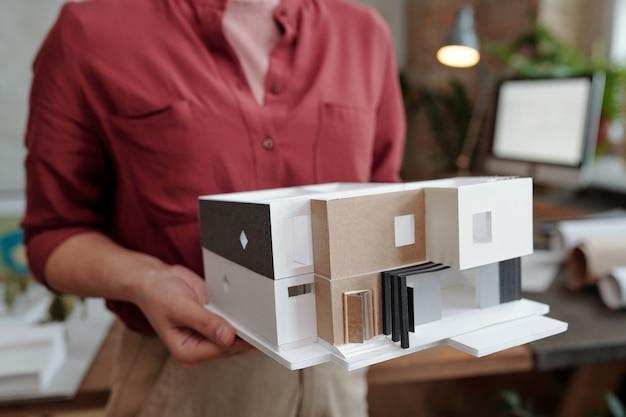 Ręka młodej kobiety architekta lub projektanta inżynierii w codziennej odzieży trzymającej papierowy model nowego domu, stojąc w biurze