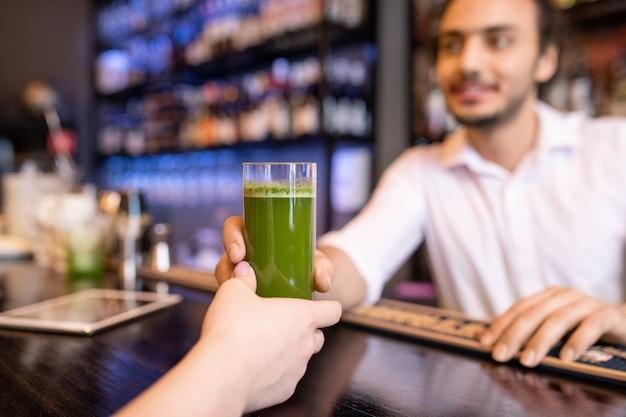 Ręka młodej kobiety biorącej szklankę świeżej pensji lub smoothie z brokułami mijanej przez kelnera lub barmana w eleganckiej restauracji