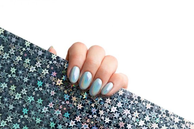 Ręka młodej kobiety dorosłej z holograficznymi modnymi paznokciami