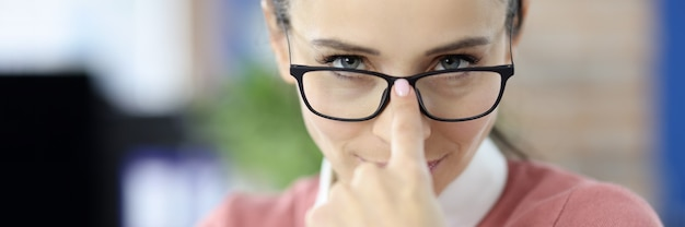 Ręka młodej kobiety dostosowującej okulary do koncepcji ścisłej wizji szefów