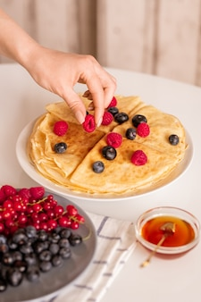 Ręka młodej kobiety lub gospodyni domowej biorąc świeże dojrzałe maliny z góry domowe naleśniki na talerzu jedząc śniadanie