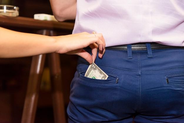 Ręka młodej kobiety wyciąga pieniądze z kieszeni mężczyzny