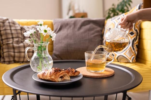 Ręka młodej kobiety z czajniczkiem wlewająca zieloną herbatę ziołową do filiżanki, idąc rano zjeść rogalika na śniadanie