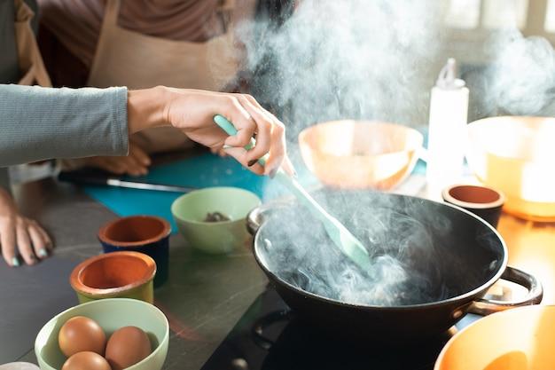 Ręka młodej kobiety z żaroodporną łopatką mieszającą składniki na patelni, stojąc przy kuchence elektrycznej podczas gotowania masterclass