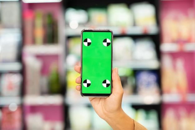 Ręka młodej współczesnej kobiety zakupoholiczki pokazująca zielony e-kupon na ekranie smartfona przed wyświetlaczem z produktami kosmetycznymi