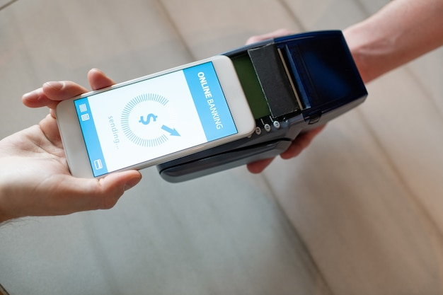 Ręka młodzieńca ze smartfonem płacącym przez bankowość internetową, trzymając swój mobilny gadżet nad maszyną płatniczą trzymaną przez kelnera