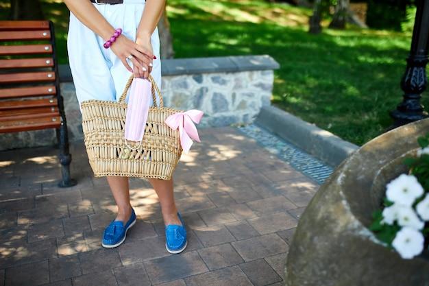 Ręka modnej kobiety wz słomkowej torbie z różową maską medyczną w torebce na zewnątrz