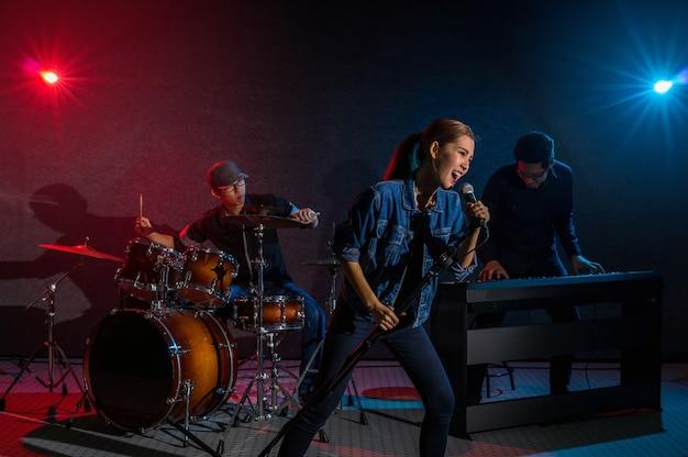Ręka muzyk zespołu trzymając mikrofon i śpiewając piosenkę i grając na instrumentach