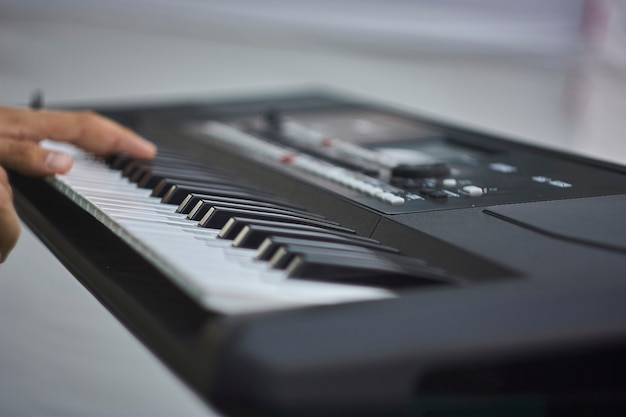 Ręka muzyka naciskającego klawisze elektronicznej klawiatury podczas grania na koncercie