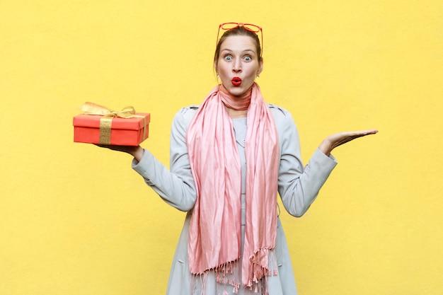 Ręka na bokach i trzymająca bożonarodzeniowe pudełko kobieta patrząca na kamerę z zszokowaną twarzą i otwartymi ustami